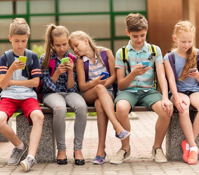 Fünf Schulkinder sitzen auf einer Bank und jedes Kind hält ein Handy in der Hand und guckt darauf