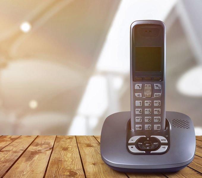 Ein kabelloses Festnetztelefon steht auf einem braunen Holztisch