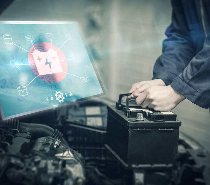 Hände, die eine Autobatterie aus dem Motorraum heben und ein Hologramm eines Displays, auf dem eine Autobatterie abgebildet ist