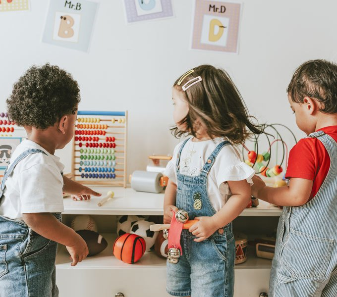 Zwei Jungen und ein Mädchen vor einem Schrank mit Spielzeug