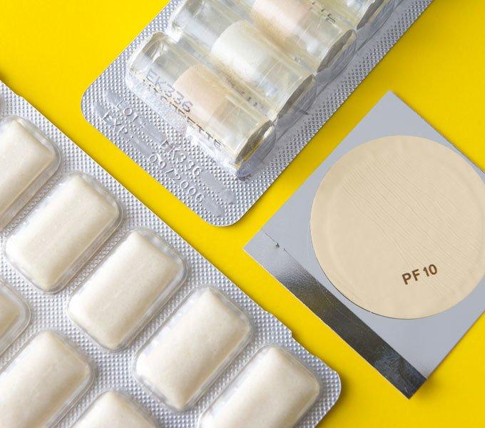 Mehrere unterschiedliche Produkte zur Raucherentwöhnung liegen auf einem gelben Untergrund