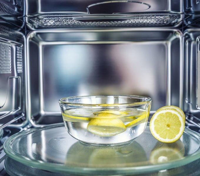 Schale mit Wasser und Zitronenscheiben in einer Mikrowelle