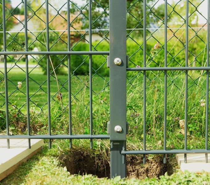 Zaunpfosten in einem für das Betonfundament ausgehobenen Loch