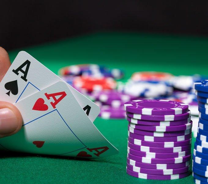 Pokerchips und zwei Asse in einer Hand