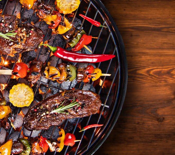 Fleisch liegt zusammen mit Gemüsespießen und anderen Zutaten auf einem Grill