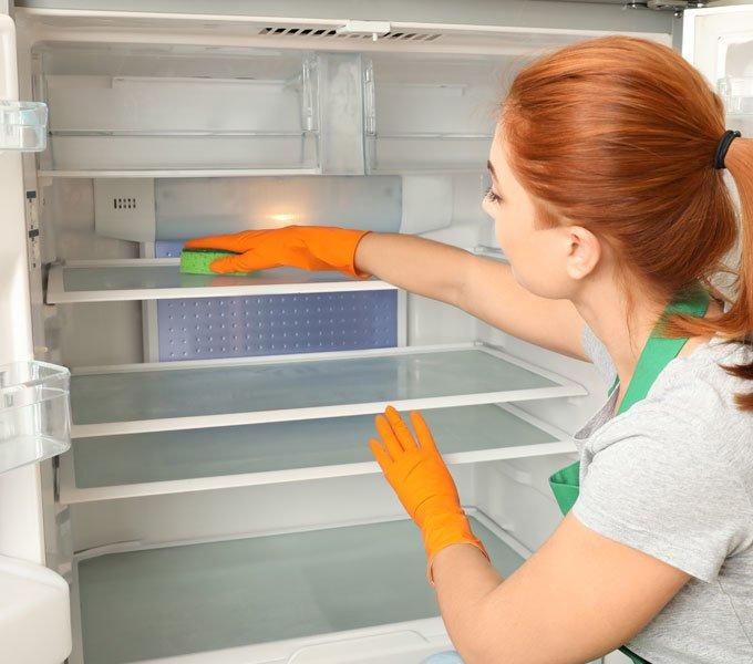 Frau reinigt mit einem Schwamm den Innenraum des leeren Kühlschranks