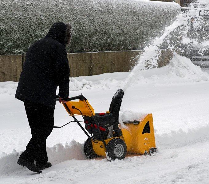 Ein Mann räumt mit einem Schneefräser seine Auffahrt frei