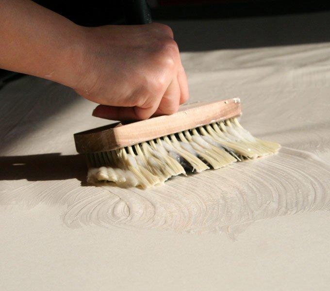 Eine junge Frau streicht den Kleister per Hand auf eine ausgerollte Tapete