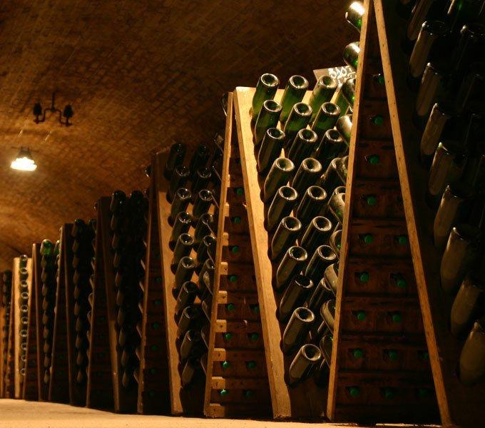 Mehrere Champagnerflaschen sind in Rüttelpulte aufgesteckt