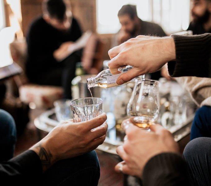 Eine Gruppe Personen sitzt um einen Tisch, sie schenken sich Whisky in ihre Gläser ein