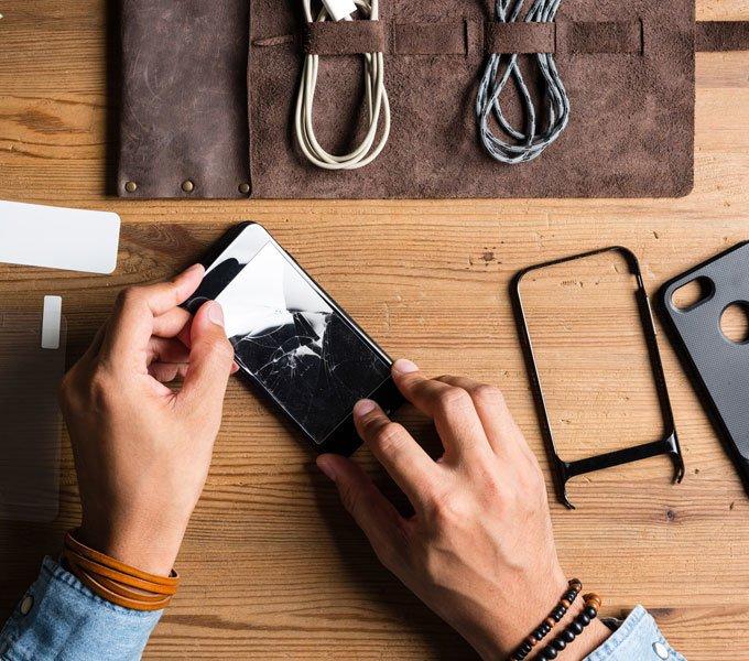 Männerhände halten ein Handy und auf einem Holztisch daneben liegen Kopfhörer, Kabel und weiteres Zubehör