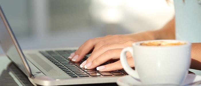 Frau sitzt mit Kaffee am Notebook