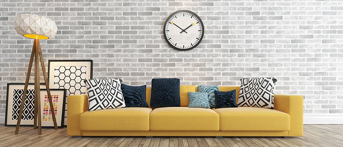 Aufnahme eines gelben Sofas und verschiedener Deko-Artikel.
