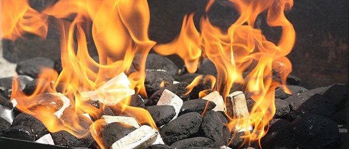 Nahaufnahme von brennenden Grillanzündern zwischen Kohle.