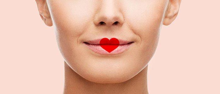 Nahaufnahme eines Mundes, auf welchem sich ein mit Lippenstift gemaltes Herz befindet.