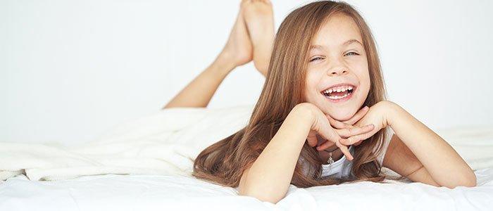 Aufnahme eines Mädchens, welches in einem weißen Bett liegt.