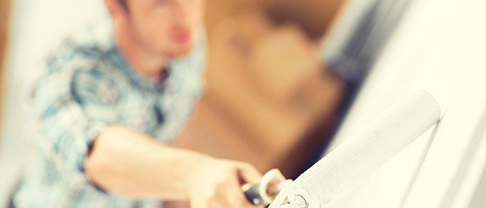 Mann streicht die Wände einer Wohnung