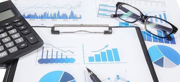 Auf einem Tisch liegende Quartalsberichte mit Taschenrechner und Brille