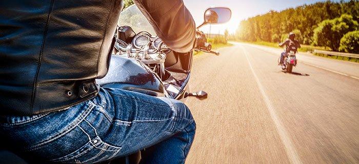 Zwei Motorradfahrer fahren auf einer Asphaltstraße der Sonne entgegen