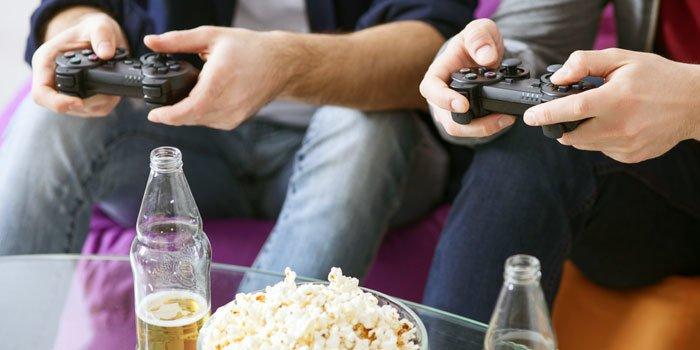 Zwei Personen sitzen mit Spielkonsolen-Controllern vor einem Tisch mit Getränken und Popcorn
