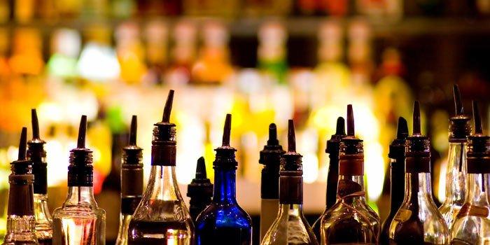 Nahaufnahme von Flaschenhälsen mit Ausschenkern in einer Bar.