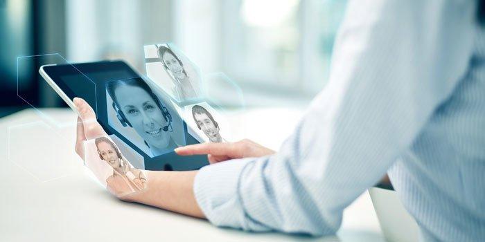 Frau betrachtet mehrere Konferenz-Teilnehmer, die per Chat zugeschaltet sind, auf ihrem Tablet.