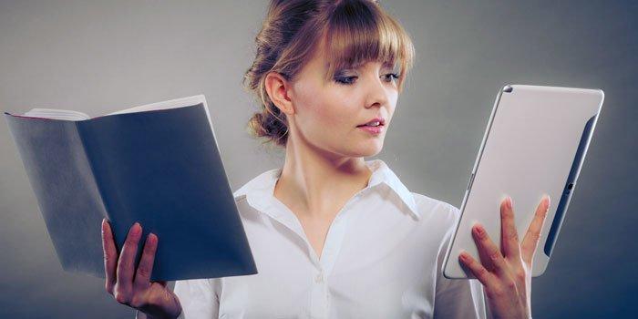 Frau hält in der einen Hand einen eBook Reader, in der anderen ein Buch.