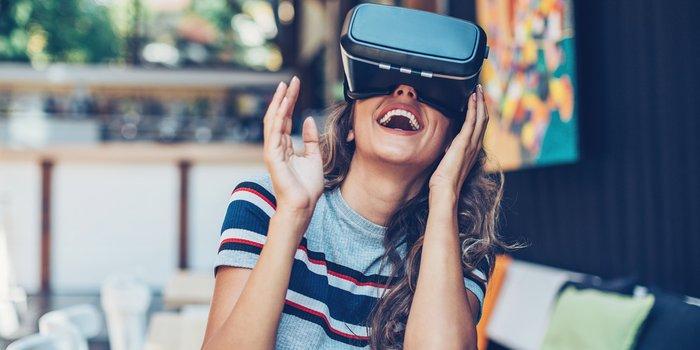 Junge Damen probiert sich mit der VR-Brille im Wohnzimmer