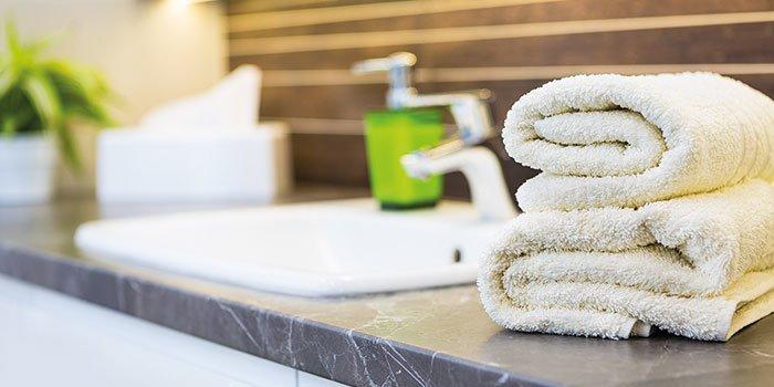 Nahaufnahme eines Waschtisches mit gerollten Handtüchern.