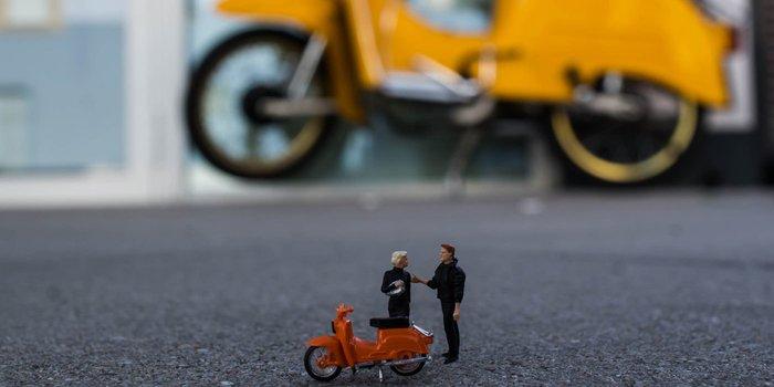 Modell eines Mopeds mit Modellfiguren vor einem Moped in Originalgröße