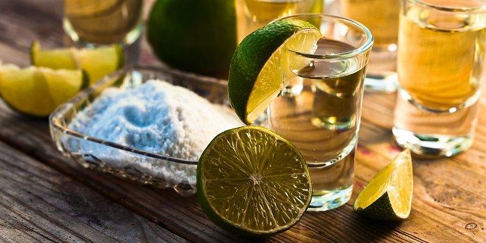 Mehrere kurze Gläser Tequila mit frischen Limetten und Salz.