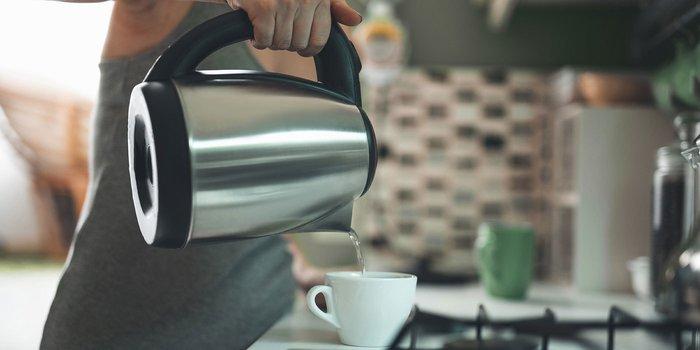 Frau, die heißes Wasser aus einem Wasserkocher in eine Tasse gießt