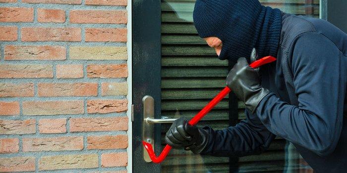 Einbrecher mit Brechstange an der Haustür