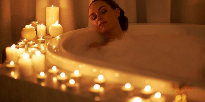 Eine junge Frau gönnt sich ein Schaumbad im Kerzenschein.