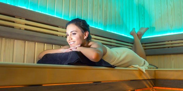 unge Frau entspannt alleine in einer blau beleuchteten Sauna