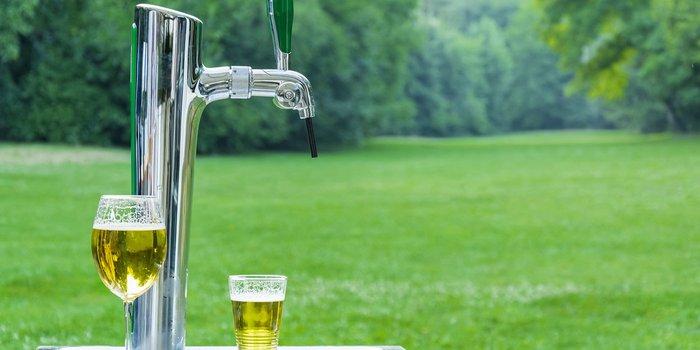 Mobile Bierzapfanlage mit zwei Gläsern Bier steht in einem Garten