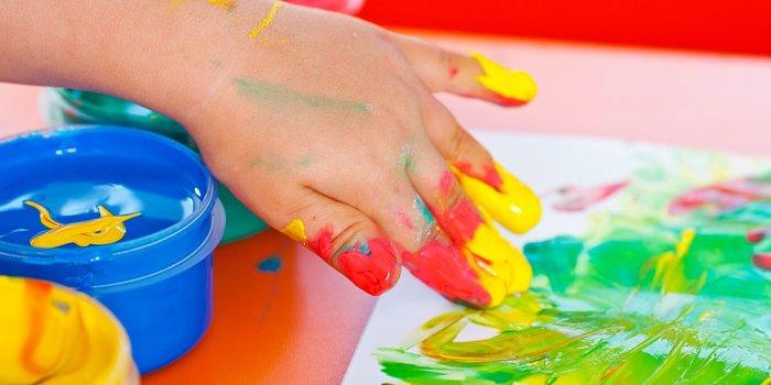 Kinderhand malt mit Fingermalfarben