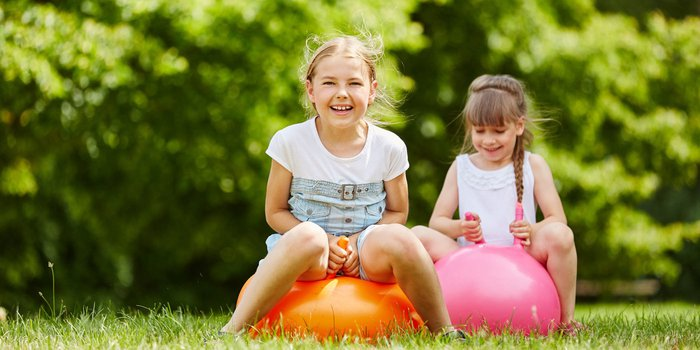 Zwei Mädchen springen auf Hüpfbällen über eine Wiese