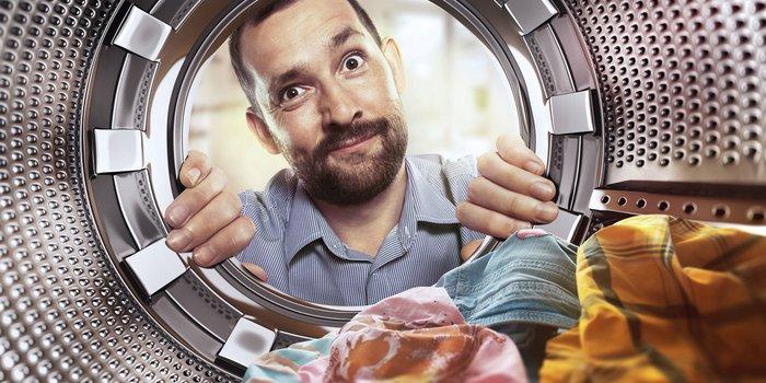 Mann mit Bart schaut fragend in die Trommel der Waschmaschine