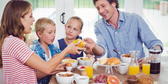 Ein Elternpaar frühstückt gemeinsam mit den zwei kleinen Kindern