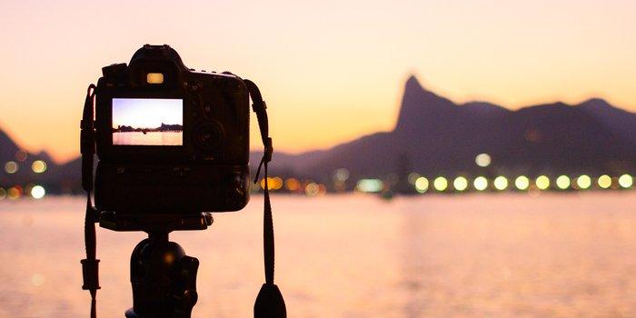 Kamera steht am Strand und zeigt auf Meer und Gebirge.