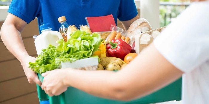 Frau nimmt Lebensmittelliefeung entgegen
