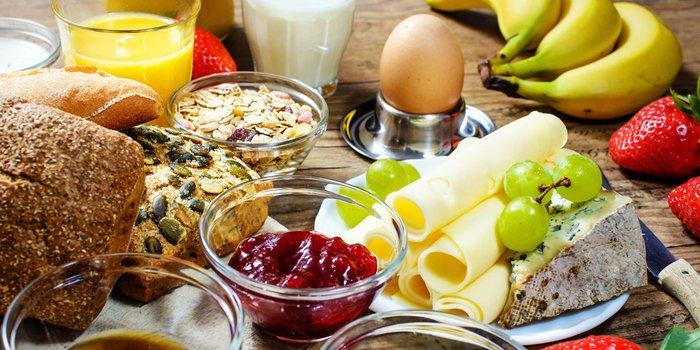 Ein ausgewogenes Frühstück mit Brötchen, Marmelade, Eiern und Käse