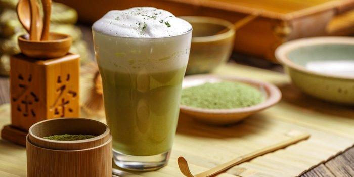 Eine Tasse Matcha Tee mit den einzelnen Bestandteilen drum herum