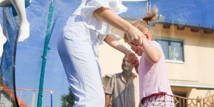 Familie springt auf einem Gartentrampolin