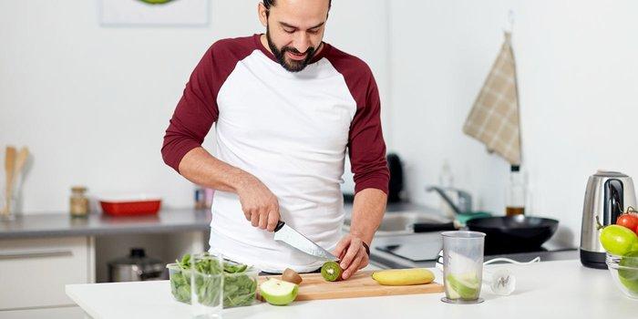 Mann zerschneidet Obst und Gemüse auf einem Brett, daneben steht ein Stabmixer