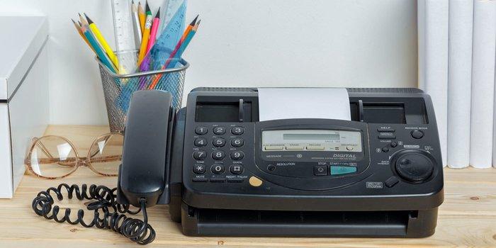 Ein Faxgerät steht vor Büchern und Büromaterialien auf einem Schreibtisch