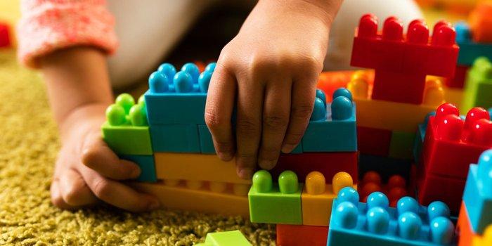 Junges Mädchen spielt mit mit Bausteinen aus Kunststoff
