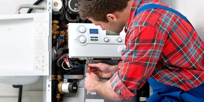 Heizungsmonteur arbeitet an einem Boiler