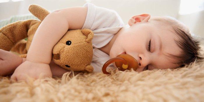 Kleiner Junge schlummert auf einem Teppich